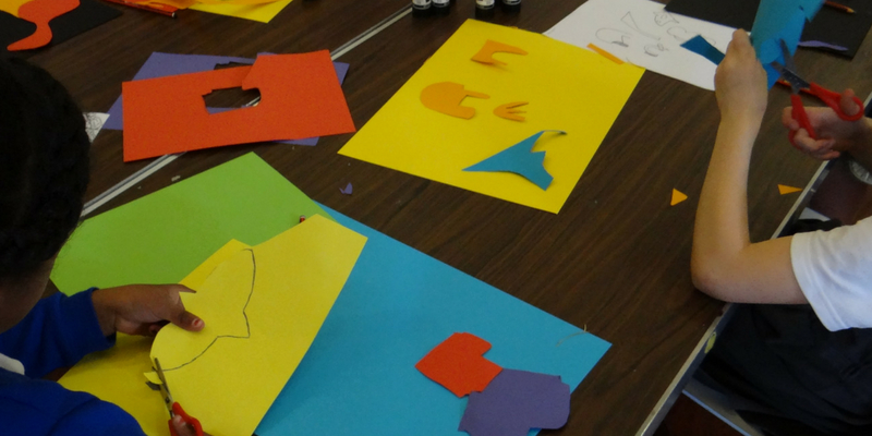 Children cutting up brightly coloured card for an artwork