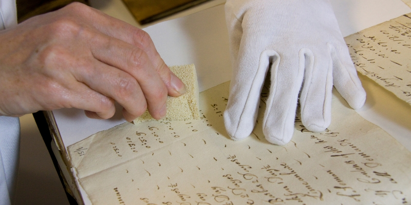 A hand wearing a white glove holding a piece of archival paper with writing on it, while another hand uses a sponge on the paper