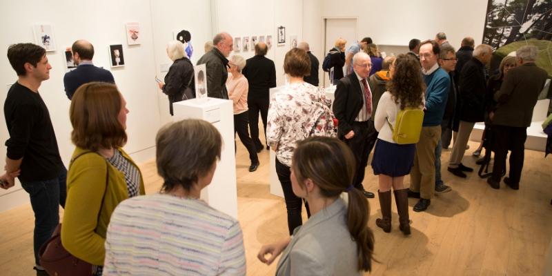 A group of visitors in the Gallery looking at artworks during an exhibition opening
