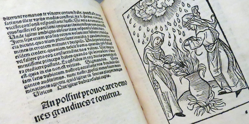 Open book pages depicting text and a woodcut image of two figures around a cauldron
