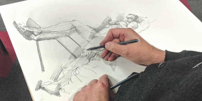 A close crop of a hand holding a pencil and drawing a reclining figure