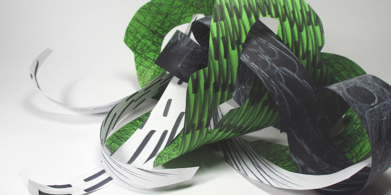 Green and black sculpture made from paper