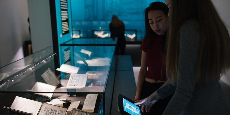 View of the Treasures of the Brotherton Gallery display with visitors interacting with an information screen