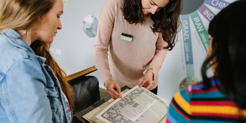 Three people gathered around looking at an open book displaying printed illustrations