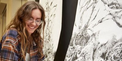 FUAM prize winner Katie Bennett-Rice sits with her work