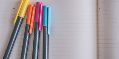 Four different coloured pens on top of a notebook