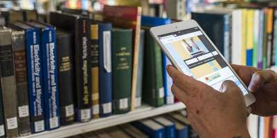 A customer uses Library Search while viewing a shelf in the Laidlaw Library