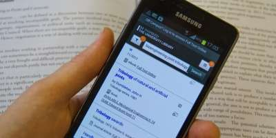 A student using a mobile phone to search the library catalogue, with a textbook in the background.