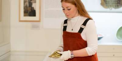 A staff member handles an object in the art gallery