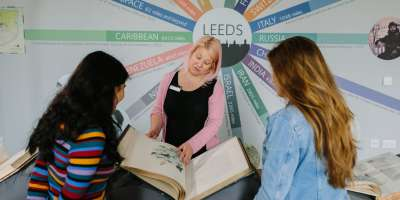 A woman stands in front of a sign saying 'Leeds'. She has a large book from Special Collections in front of her and she is presenting it to two students.