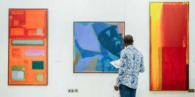 A man stands staring at 3 brightly coloured paintings in The Stanley &   Audrey Burton Gallery
