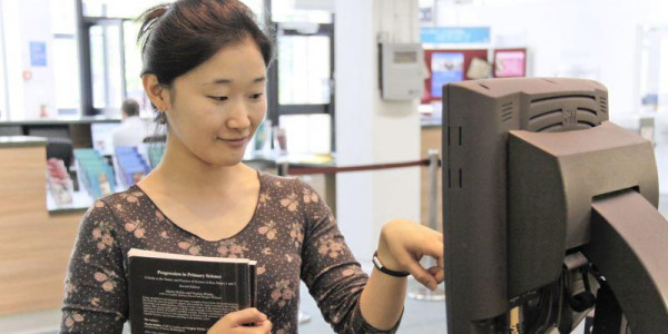 A student borrowing a book using a self service machine
