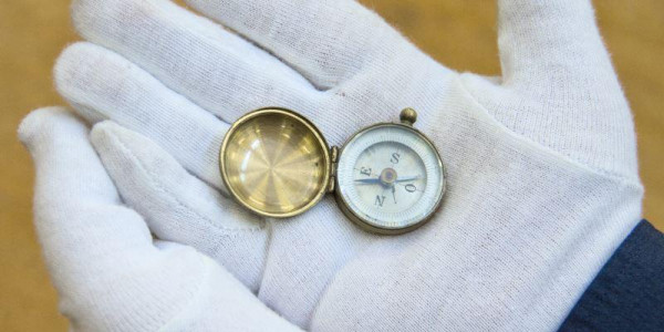 Gloved hands holding a compass